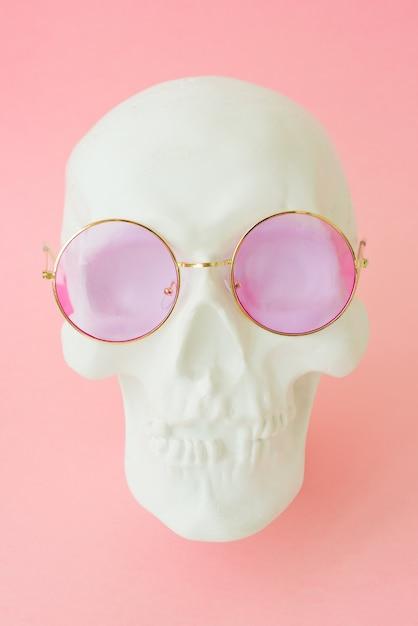 Witte menselijke schedel met roze bril. detailopname Premium Foto