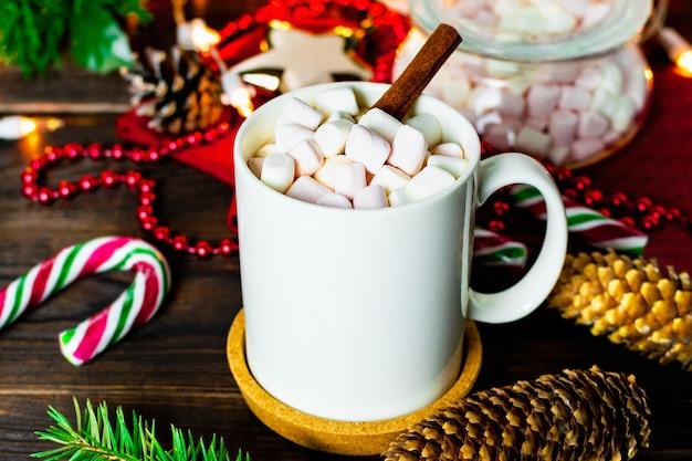 Witte mok cacao met marshmallows, lollys, dennenappels, kerstboomtak, slinger en sneeuwvlok op houten tafel Premium Foto