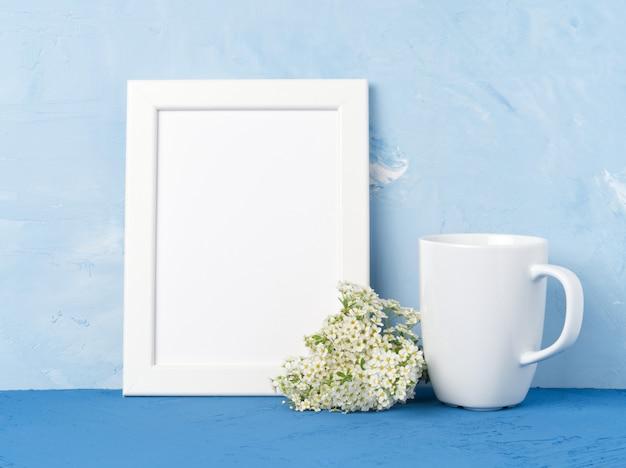 Witte mok met thee of koffie, frame, bloemboeket op blauwe tafel tegenover blauwe muur. Premium Foto