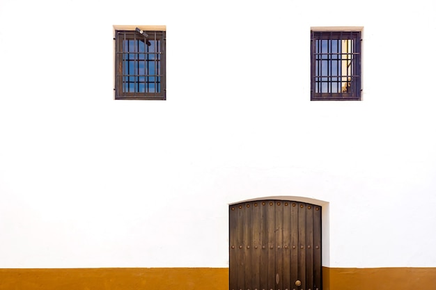 Witte muur met deur en twee gezichtsvormige ramen. Premium Foto