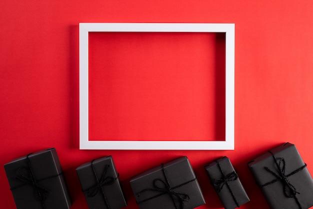 Witte omlijsting met zwarte geschenkdoos op rode achtergrond. black friday-concept Premium Foto