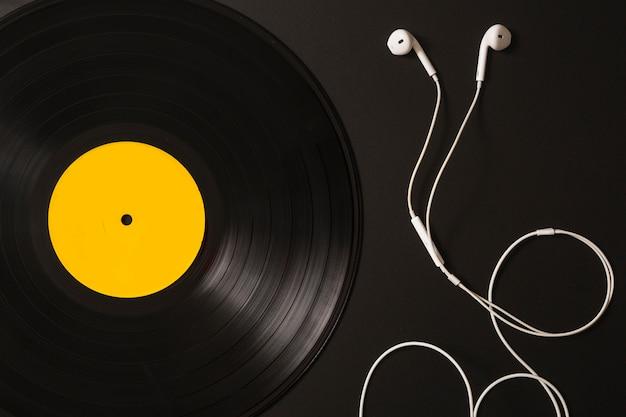 Witte oortelefoons en vinylverslag op zwarte achtergrond Gratis Foto
