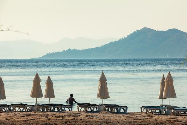 Witte parasols, blauwe zee en grote bergen aan de horizon Premium Foto