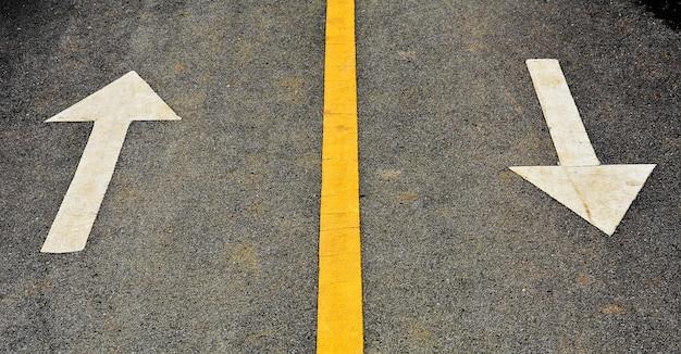 Witte pijl geschilderd op asfaltweg Premium Foto