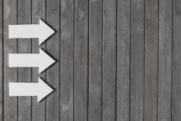 Witte pijlen op houten achtergrond Gratis Foto