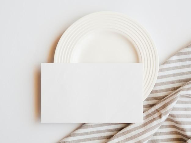 Witte plaat met een witte blanco en een gestreept bruin en wit tafelkleed op een witte achtergrond Gratis Foto