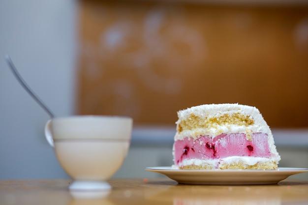 Witte plaat met verse heerlijke lekker zelfgemaakte stuk fruit koekje witte en roze romige cake op keukentafel op porseleinen beker op licht wazig kopie ruimte Premium Foto