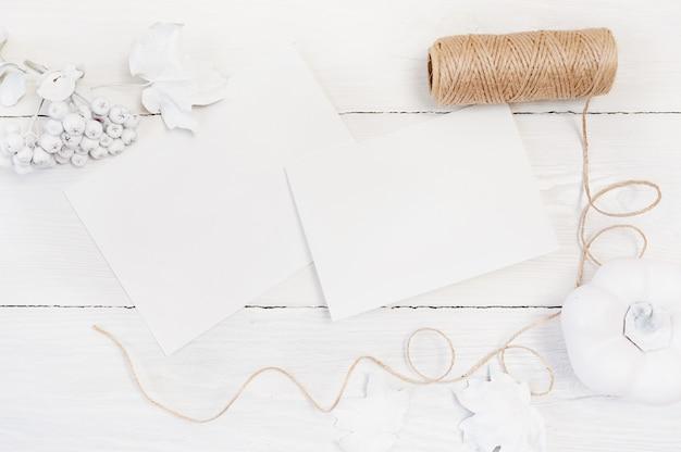 Witte pompoen, bessen en bladeren en twee witte vellen papier Premium Foto