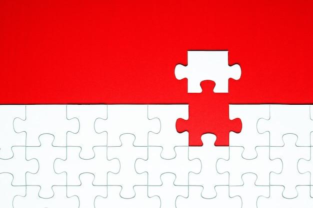 Witte puzzelstukjes op een rode achtergrond gescheiden Premium Foto
