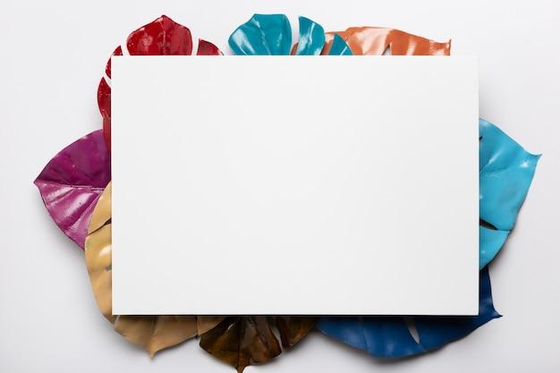 Witte rechthoek met kleurrijke bladeren eronder Gratis Foto