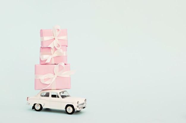 Witte retro speelgoedauto met roze geschenken Premium Foto