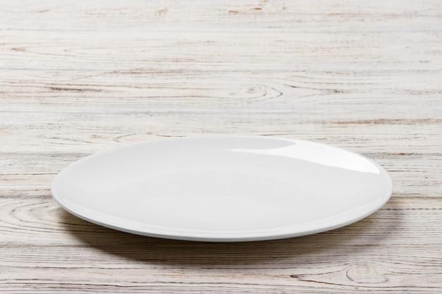 Witte ronde plaat op witte houten tafel achtergrond. perspectief Premium Foto