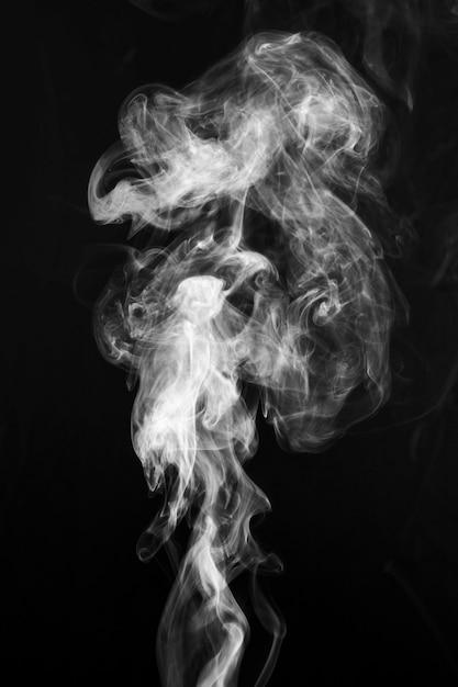 Witte rook die uit wijd over donkere achtergrond wervelt Gratis Foto