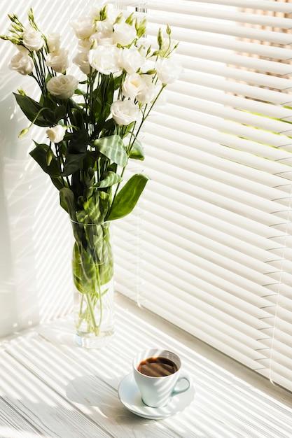 Witte roze bloemenvaas en koffiekop dichtbij vensterzonneblinden Gratis Foto