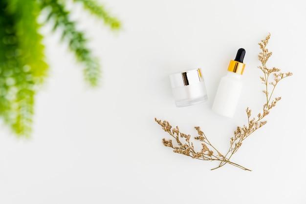 Witte serumfles en zalfpot, mockup van schoonheidsproductmerk. hoogste mening over de witte achtergrond. Premium Foto