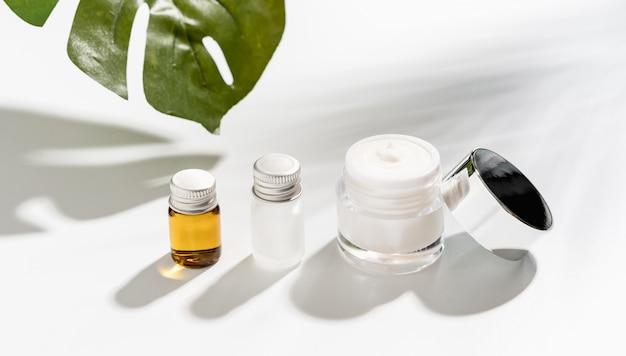 Witte serumfles en zalfpotje, schoonheidsproductmerk. bovenaanzicht op de witte achtergrond. Premium Foto