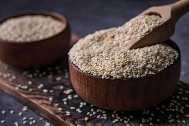 Witte sesam in een houten lepel op donkere tafel, sesamolie in pot en zaden. Premium Foto