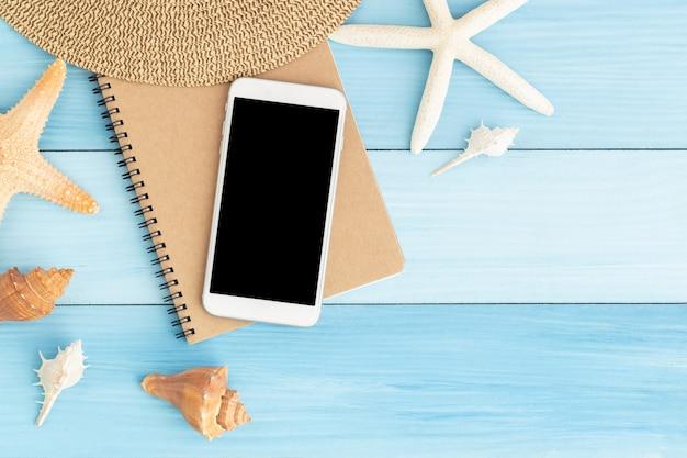 Witte smartphone op bruin notitieboekje op blauwe houten Premium Foto