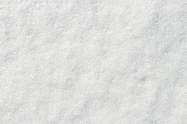 Witte sneeuw die op de de textuur natuurlijke achtergrond van het zonclose-up glanst Premium Foto