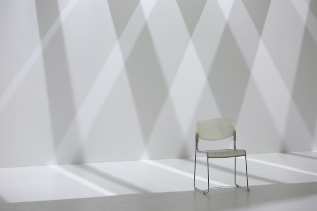 Witte stoel voor de schaduwmuur van de diamantvorm Premium Foto