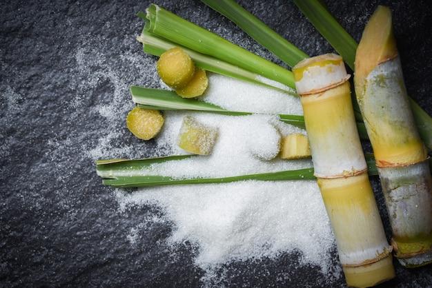 Witte suiker en en groen van blad gesneden stuk suikerriet Premium Foto