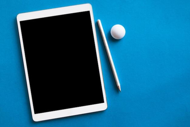 Witte tablet en potlood op blauwe oppervlak Gratis Foto