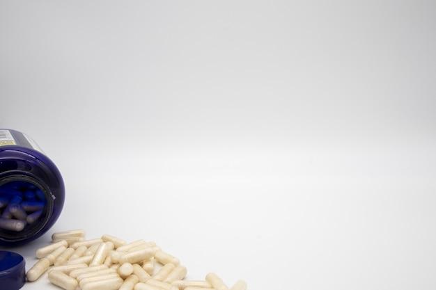 Witte tabletten uit een blauwe pil fles Gratis Foto