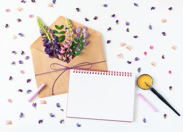 Witte tafel ligt een envelop, notitieboekje, vulpen en bloemen Premium Foto
