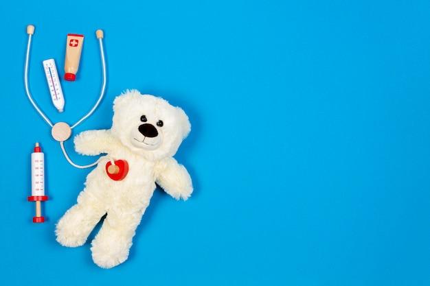 Witte teddybeer met speelgoed stethoscoop en speelgoed geneeskunde tools Premium Foto