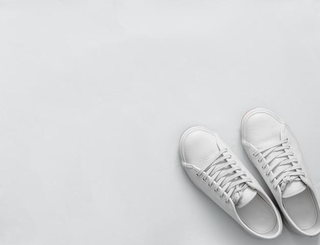 Witte tennisschoenen op lichte achtergrond, exemplaarruimte Premium Foto