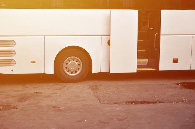 Witte toeristenbus voor excursies. de bus staat geparkeerd op een parkeerplaats in de buurt van het park Premium Foto