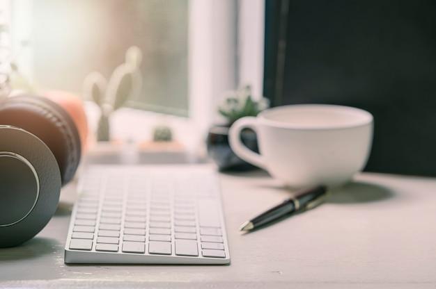 Witte toetsenbordcomputer, boeken en levering op houten lijst met zonlicht over venster, werkruimteconcept. Premium Foto