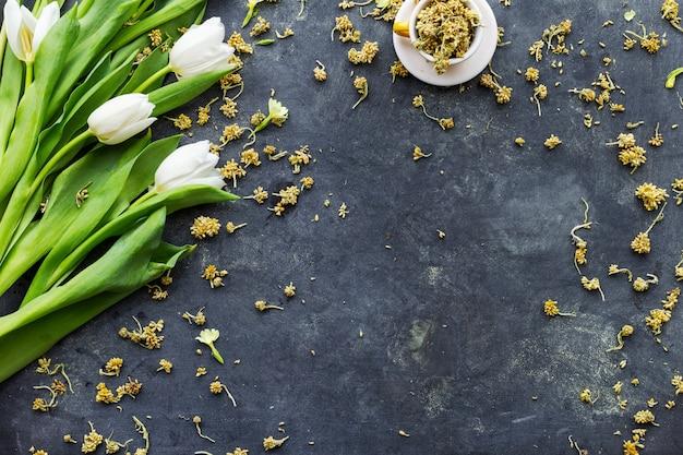 Witte tulpen met gedroogde bloemen in een kopje op een zwarte ondergrond Gratis Foto