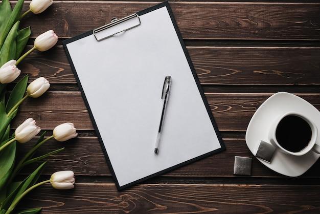 Witte tulpen op een houten tafel met een lege papieren tablet en een kopje koffie Premium Foto