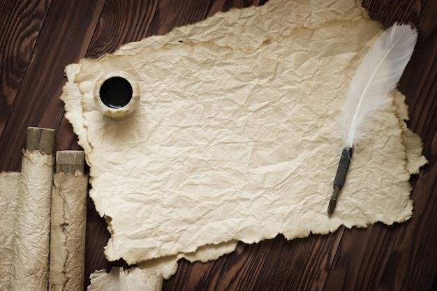 Witte veren en oude bladeren op bruine plank Premium Foto