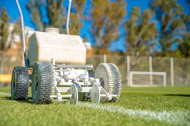 Witte verf op het gras spatten om de machine te helpen de grenzen van een voetbalveld te markeren. Premium Foto
