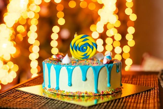 Witte verjaardagstaart met snoep en kaars voor kleine babyjongen en decoraties voor cake smash Premium Foto