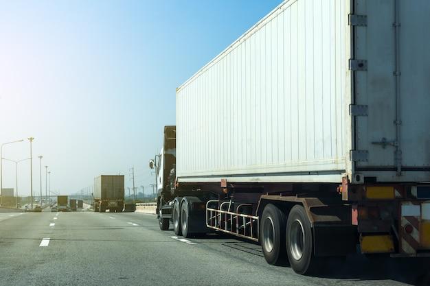 Witte vrachtwagen op wegweg met container, logistisch industrieel vervoer Premium Foto