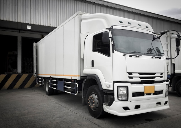 Witte vrachtwagens die ladingslading dokken bij distributiemagazijn Premium Foto