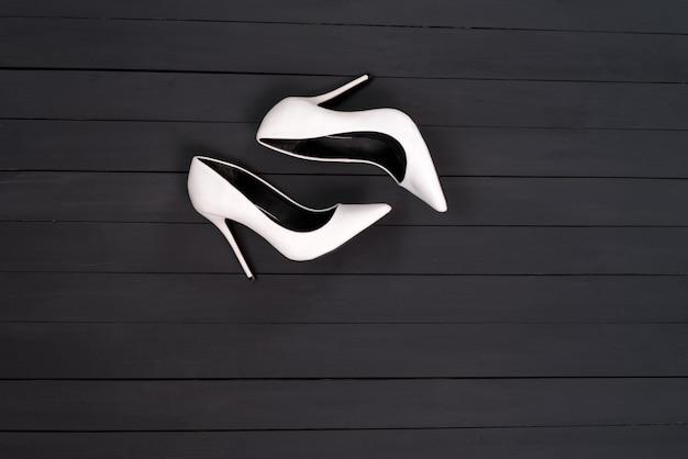 Witte vrouwelijke schoenen op een zwarte houten ondergrond Premium Foto