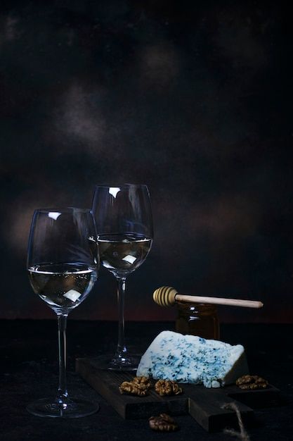 Witte wijn in fijn glas met blauwe kaas, honing, walnoten op donker Gratis Foto