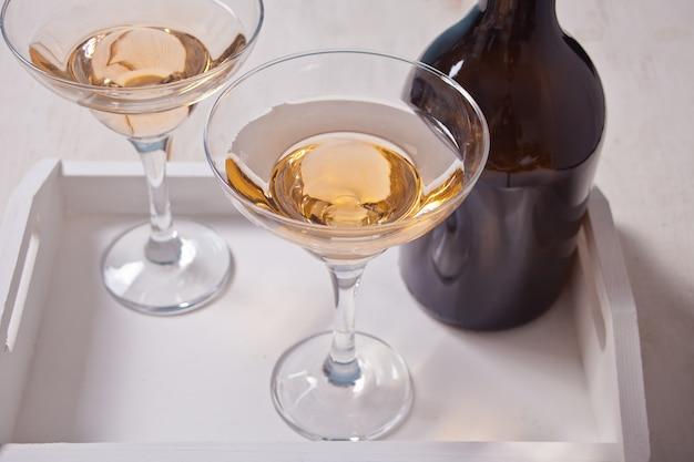 Witte wijn in glazen, fles op het witte houten dienblad. diner voor twee. Premium Foto