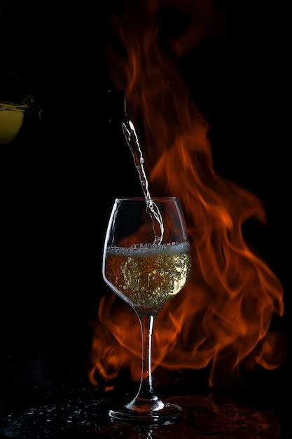 Witte wijn wordt op glas gegoten met lange steel in donkere backgrond met vuur Gratis Foto