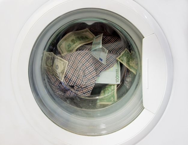 Witwassen van dollars en euro's in een wasmachine samen met linnengoed. Premium Foto