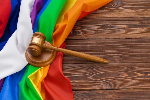 Woden rechter hamer symbool van wet en rechtvaardigheid met lgbt vlag in regenboogkleuren op houten Premium Foto