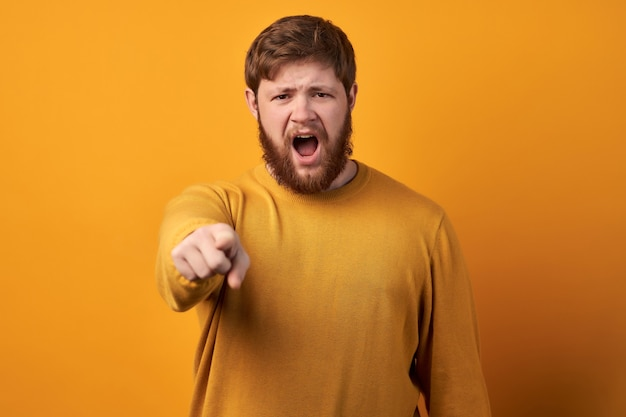 Woedende, boze ongeschoren man verliest zijn humeur, wordt gek, schreeuwt van irritatie en wijst naar je, geeft iemand de schuld en drukt negatieve emoties uit, draagt vrijetijdskleding, geïsoleerd op roze achtergrond Premium Foto