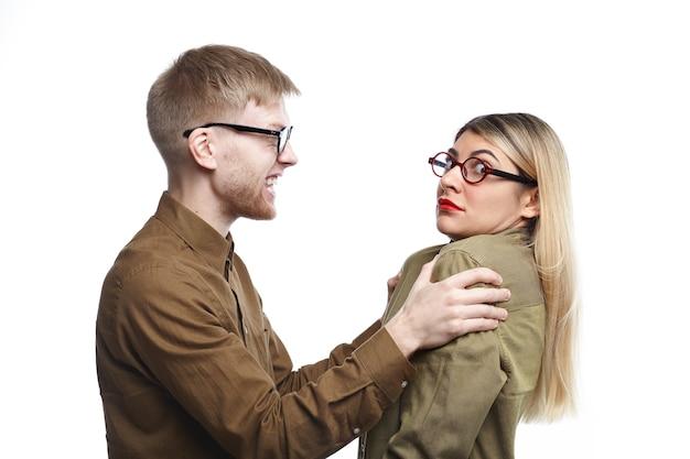 Woedende jonge bebaarde man in brillen schudt zijn bange vrouw door haar schouders. bang vrouw in glazen wordt misbruikt door haar boze echtgenoot. mensen, huwelijk, misbruik en huiselijk geweld concept Gratis Foto