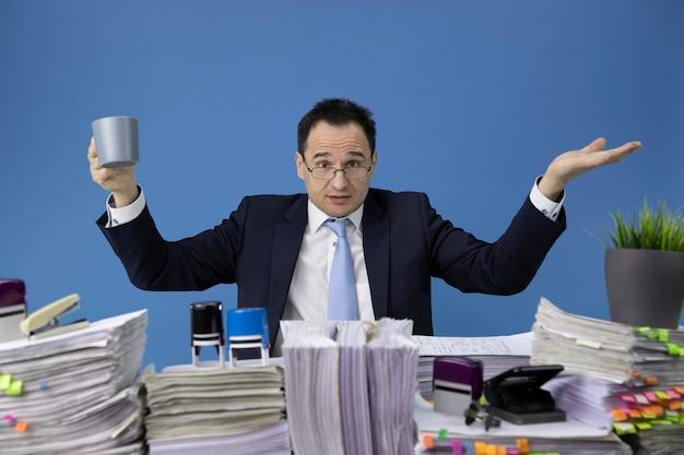Woedende zakenman zwaait met zijn handen over een bureau vol documenten Premium Foto
