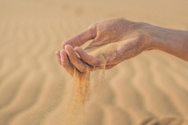 Woestijn, zand blaast door de vingers van een mannenhand Premium Foto