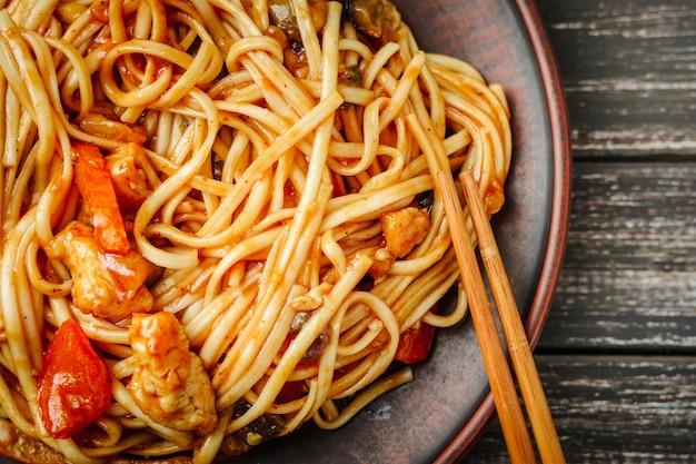 Wok udon roerbak noedels met kippenvlees in zoetzure saus op donker Premium Foto